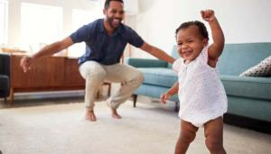 Baby Daughter Dancing With Father At Home