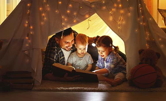 happy family father and children reading a book in tent at home