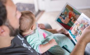 a man reading to a baby